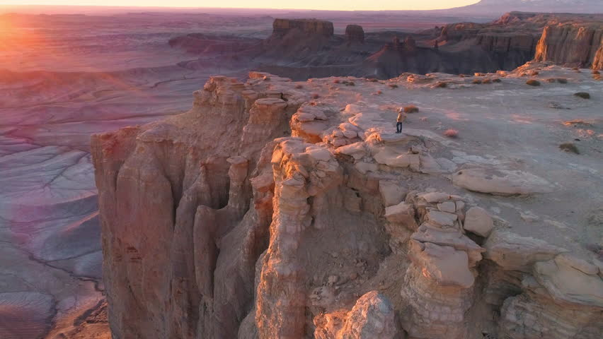 Aerial view flying past man on top of rocky cliffs during colorful sunrise at the Moonscape overlook in the Caineville, Utah desert near Factory Butte.