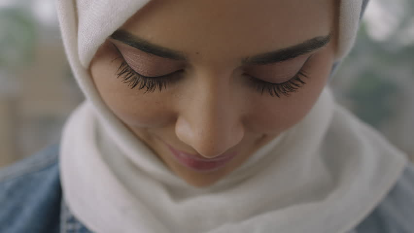 close up portrait of young muslim business woman looking up at camera confident wearing traditional hijab headscarf in office workspace background slow motion