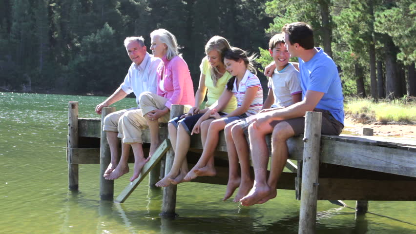 Multi-generation family sitting in on wooden jetty at edge of lake.Shot on Canon 5D MkII at 25fps