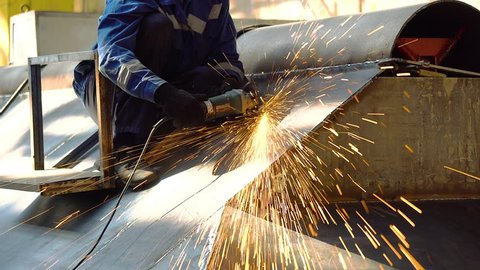 work on metal in the factory, Industrial worker in manufacturing plant grinding, worker conducts welding work, Welder welding a metal in workshop, The grinding wheel contact with the iron causes spark