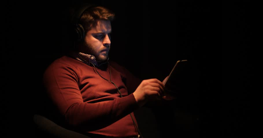 Young Man Use Headphones on Computer Digital Tablet Home in darknes