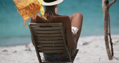 attractive woman in teak chair reading a book on a tropical beach