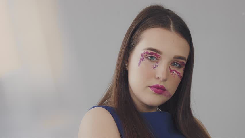 Young model with a fashin makeup in magenta tones in studio shoot closeup portrait with flairs | Shutterstock HD Video #1009570166