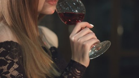 A pretty girl tasting red wine in a wine cellar. Slow motion. Close-up. Vertical pan.  A glass of wine in her hand. The face of the girl in profile. She takes a sip and looks up.