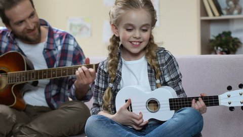 Father guitar and daughter ukulele playing song, creative leisure, rehearsal
