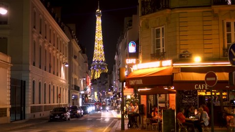 PARIS, FRANCE- CIRCA August 2017: People having dinner at parisian cafe at evening. View of famous french landmark Eiffel Tower sparkling at night. Street Rue Saint-Dominique full of people