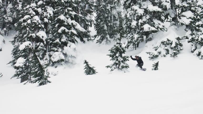 Man Snowboarding Through Trees Snow Turning Down Slope Spray Deep Powder in Air Crash Falling Blooper Winter Extreme Sports
