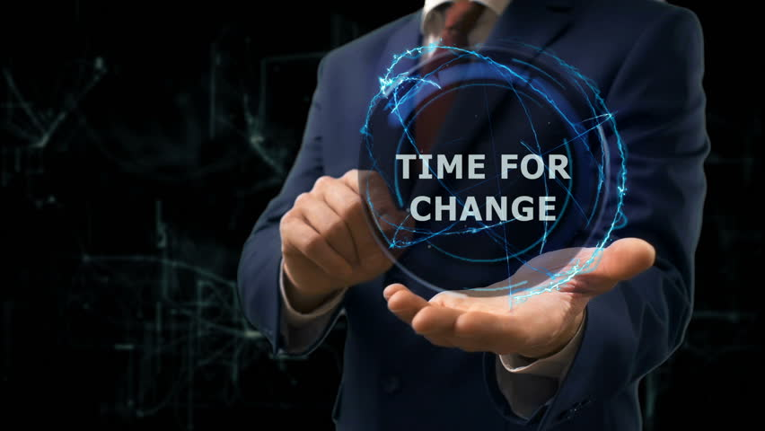 Businessman shows concept hologram Time for change on his hand. Man in business suit with future technology screen and modern cosmic background