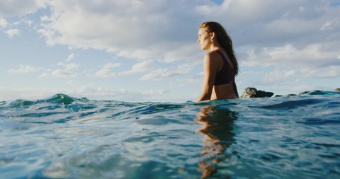 Beautiful young woman surfing at sunset, underwater view