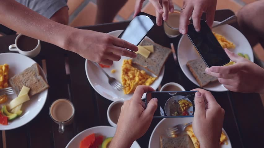 Three friends take pictures on the phones of a delicious colorful breakfast, top view. Slow motion. HD, 1920x1080