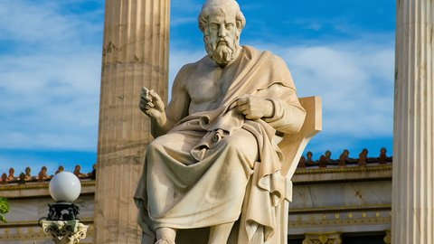 Statue of the great Greek philosopher Plato on a marble chair, background of sky and marble columns.