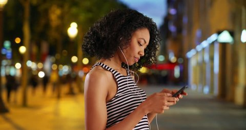 Stylish young Black woman texting and listening to music on phone in the city at night. Millennial using smartphone and waiting for friend on warm summer evening. 4k