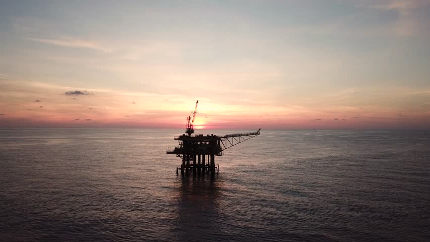 Aerial view from a drone of a small offshore platform in the middle of the ocean during sunset