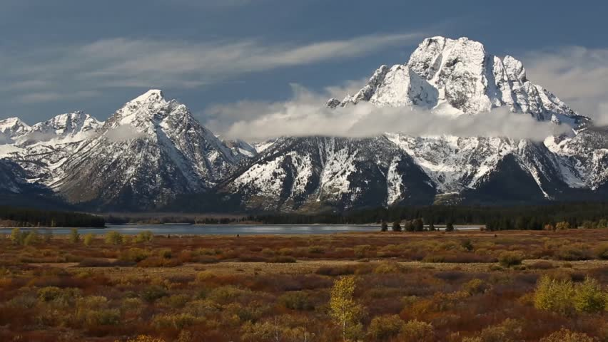 Trip to National park Yellowstone, Canada. Beautiful nature of meadow, water and majestic mountains covered by clouds.