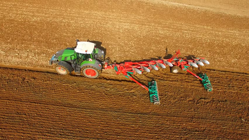 Aerial: Tractor plowing a agricultural field - aerial view - Tractor cultivating arable land for seeding crops, aerial view - 4K UHD - germany