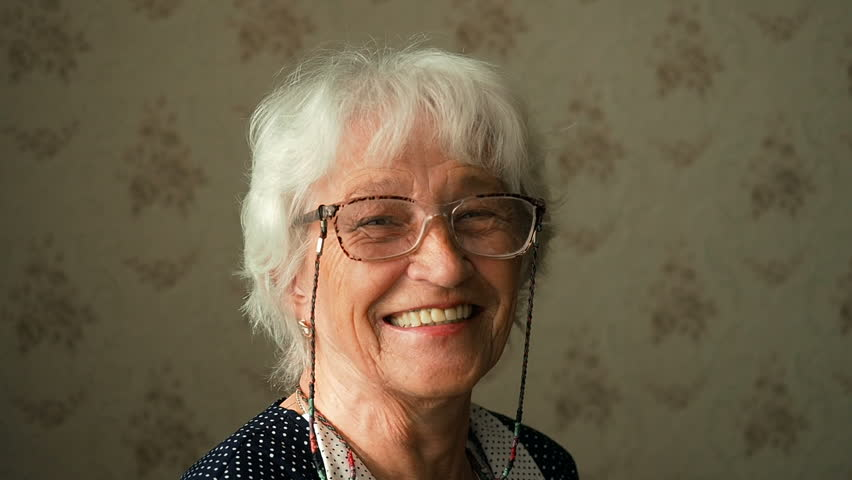 Portrait Of A Happy Grandmother. Happy elderly woman with eyeglasses smiling and looking into a camera.  | Shutterstock HD Video #1009726466
