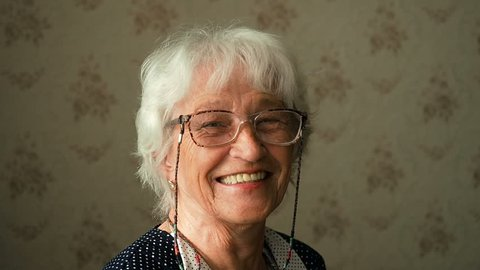 Portrait Of A Happy Grandmother. Happy elderly woman with eyeglasses smiling and looking into a camera.
