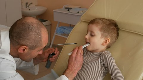 Very Cute Little Boy Opens His Mouth to the Doctor Looked at His Throat. Little Boy Having Throat Examination. male doctor pediatrician, otolaryngologist, inspects a cute little boy's throat.