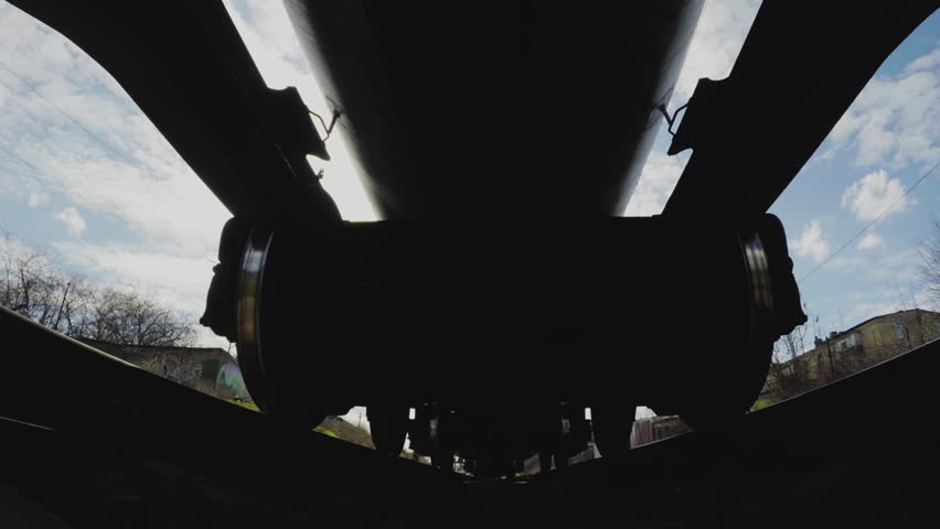 A view from below on the railway and freight train in motion. Close-up of the wheels. The camera on the sleepers under the train. Dangerous. Travel concept