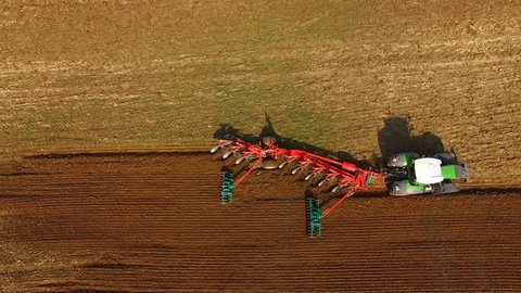 Tractor plowing a agricultural field - aerial view - Tractor cultivating arable land for seeding crops, aerial view - 4K UHD - germany