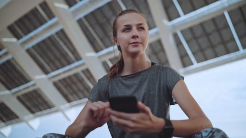 Beautiful young fitness woman resting after training outdoor using modern smartphone device checking her progress, cute smiling sportive girl texting message on cellphone, Slow motion, Lifestyle