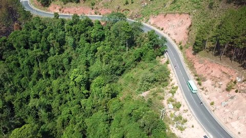 Top view. Aerial view road and forest from drone. Royalty high-quality free stock video footage of road in forest. Road in forest is beautiful with many tree, road on pass very winding and curve