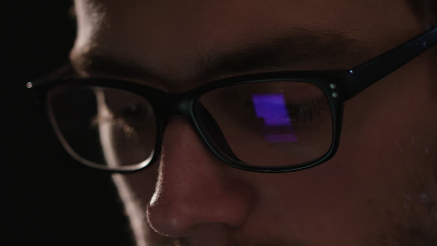 A close-up of a young man's face against a black background. Macro shot #1009789706