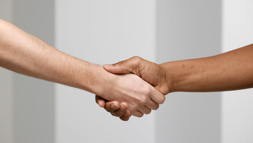 Two multiethnic men handshaking closeup, isolated over white background in slow motion, greeting or partnership concept