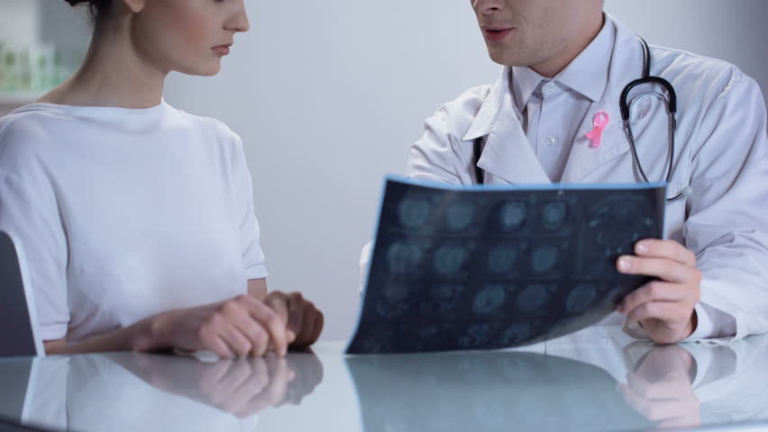 Oncologist informing woman about no threat of breast cancer, both smiling