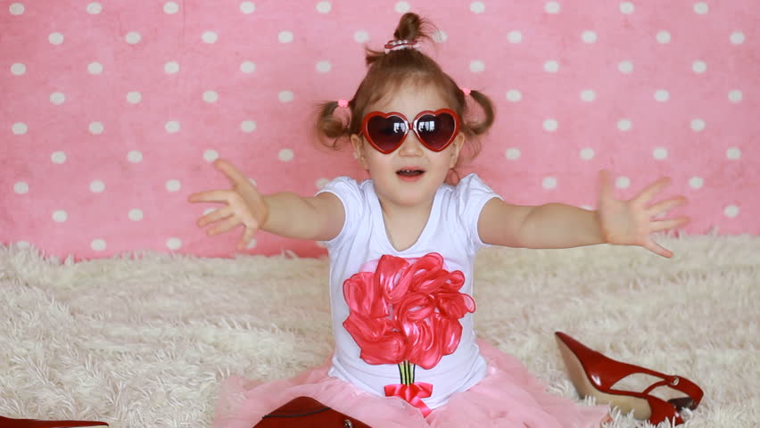 Sweet little girl in red sunglasses in the shape of hearts sends air kisses. Funny child send kiss. Pink background. Fashionista. Heart. Love