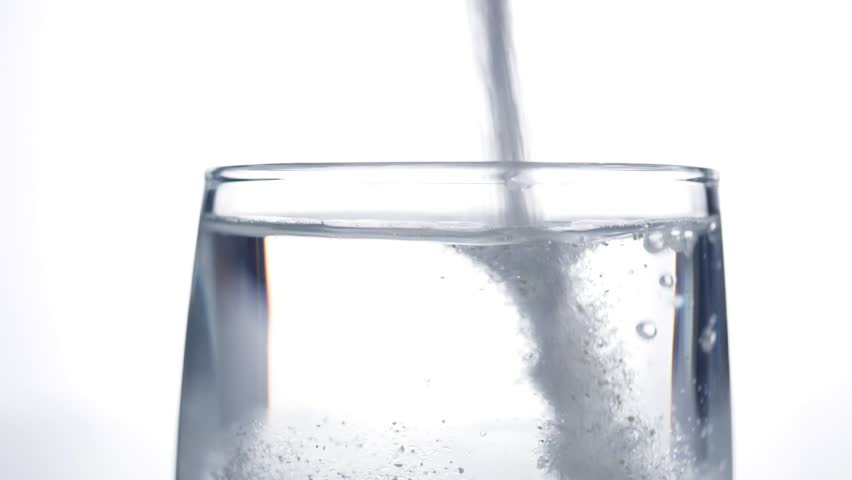 Medicine powder falling down in glass with water