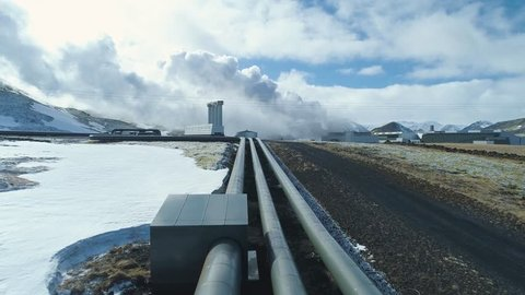 Pipes leading to Geothermal Power Plant. Steam are generated in the background. Snowy environment