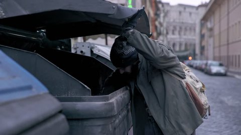 hunger, misery, poverty-bum rummages in the dumpster in the street
