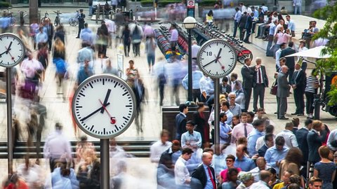 London, England. Circa, 2016. Time lapsed view of commuters walking  past the Six Public Clocks on Reuters Plaza, Canary Wharf. Financial district.