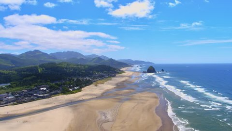 Aerial view panning left starting at Haystack Rock and continuing in land to show the town of Cannon Beach at 400 feet above the sand