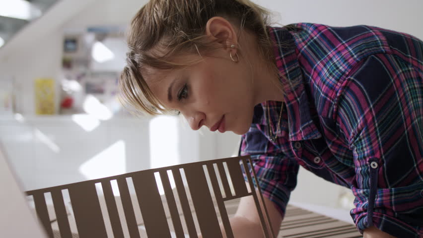 University student of Interior Design doing homework, reviewing and preparing housing model. Business woman working as architect and building mock-up   Shutterstock HD Video #1009886966