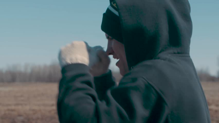 Young attractive MMA fighter shadow boxes while out for a morning run on a cold sunny morning in slow motion