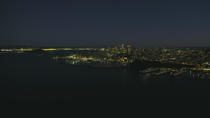 Aerial illuminated night cityscape view of San Francisco city skyscrapers Oakland Bay bridge Fishermans Wharf Pier 39 North Beach California America