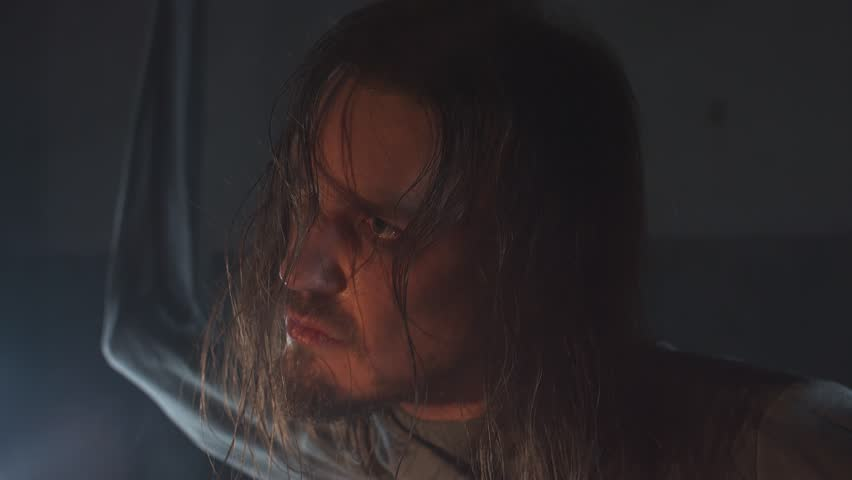Mad long haired caucasian man with straitjacket sleeves tied to ceiling in abandoned building