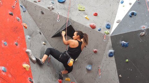 Pretty young athletic girl climbing on an indoor rock-climbing wall.