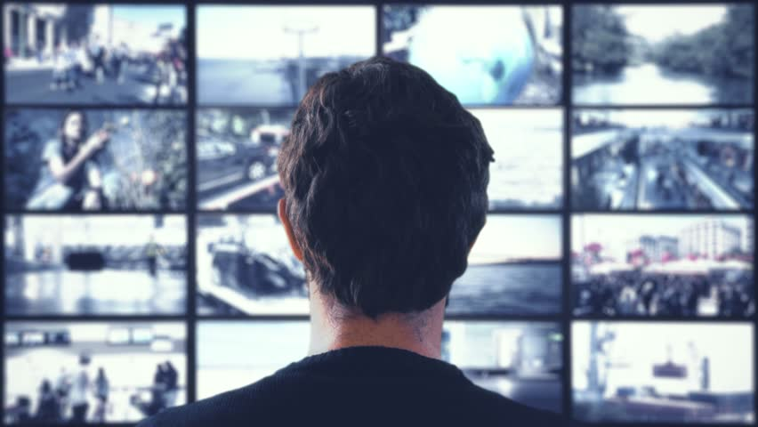 Monitoring CCTV Cameras. Head shot of a man watching CCTV cameras in a wall of monitors | Shutterstock HD Video #1009950476