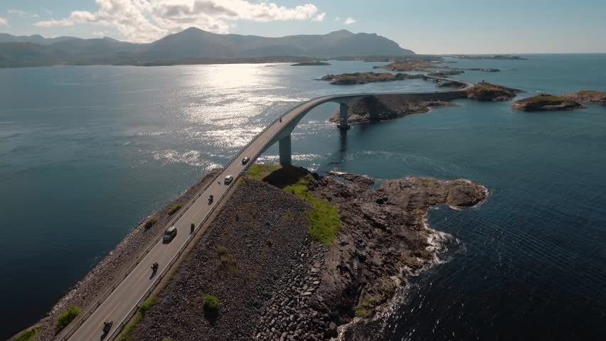 """Aerial view of motorcycles and bikers on Atlantic Road (Atlanterhavsveien) also known as """"The Road in the Ocean"""" in Norway. National Tourist Route."""