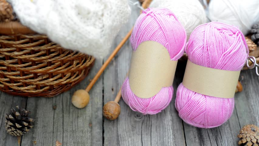 Closeup two pink balls of wool threads with empty labels lying on vintage wood desk with knitting needles and basket. Mock up background for your craft knitting logo or label   Shutterstock HD Video #1009966196