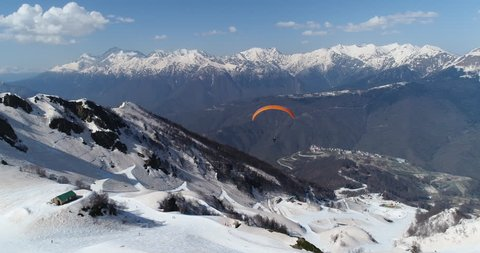 Paraglider flying over snowy mountains.