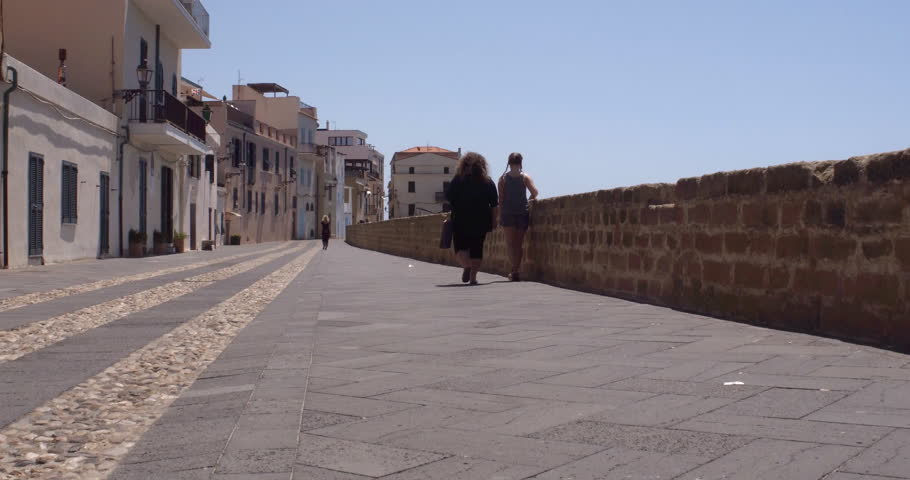ALGHERO, SARDINIA, ITALY – JULY 2016 : Video shot of couple walking on city walls in central Alghero on a sunny day