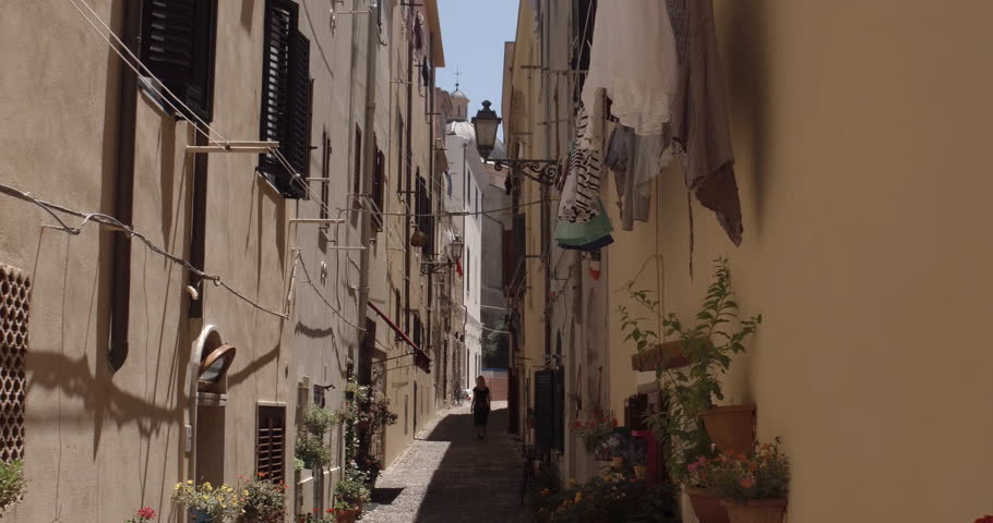 ALGHERO, SARDINIA, ITALY – JULY 2016 : Video shot of beautiful blonde girl walking in narrow street in central Alghero on a sunny day