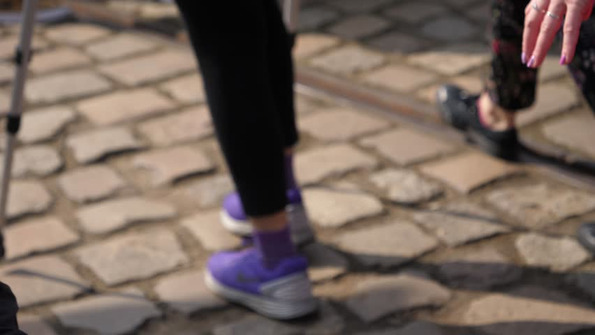 WROCLAW, POLAND - APR 07, 2018: Female legs in sneakers walks with help of crutches on a city cobblestone crowd place | Shutterstock HD Video #1009993736
