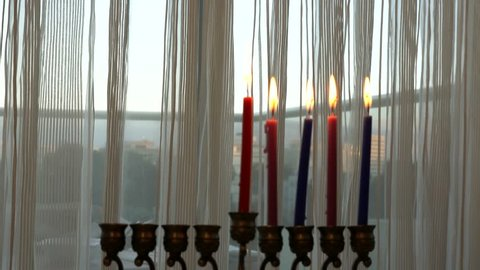 Five candles are burning on light curtain background on the fourtj day of the Jewish holiday Hanukkah. Selective focus on curtain and window. 4k