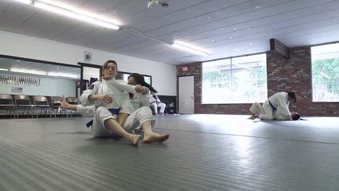 Young women practicing Jiu-jitsu in a dojo