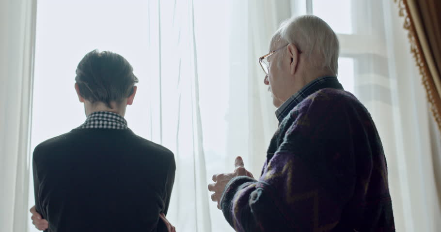 Anxious man waiting at a window staring out turning as he becomes aware of an old man behind them and then moving into an embrace of comfort. | Shutterstock HD Video #1010008556